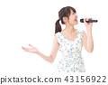 一位在卡拉OK唱歌的年轻女士 43156922