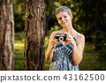 portrait of a beautiful woman with a camera in a summer forest 43162500
