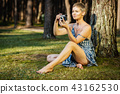 beautiful woman takes pictures with the camera in summer forest 43162530