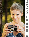 portrait of a beautiful woman with a camera in a summer forest 43162631