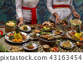 Waiter is serving table with different dishes.  43163454