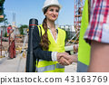 Architect and engineer or supervisor shaking hands on the construction site 43163769