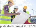 Experienced architect analyzing a blueprint on the construction site 43163770