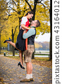 Bavarian couple in Tracht in loving embrace with uplift 43164012