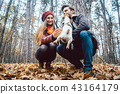 Couple of woman and man playing with their dog in fall 43164179