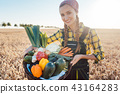Harvest time in the country, woman farmer offering vegetables 43164283