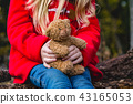 little girl holding a bear toy 43165053