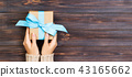 Woman hands give wrapped present 43165662