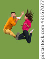 Beautiful young couple jumping with megaphone isolated over green background 43167077