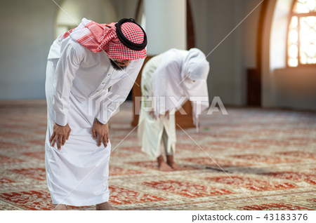 Muslim man and woman praying in mosque 43183376