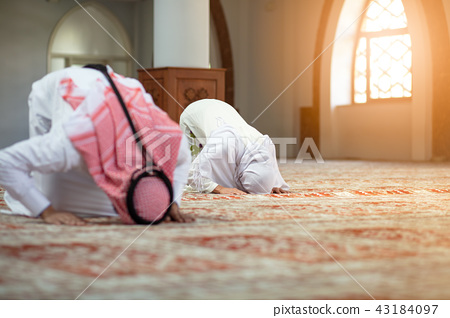 Muslim man and woman praying in mosque 43184097