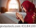 Young muslim woman praying in mosque with quran 43184100