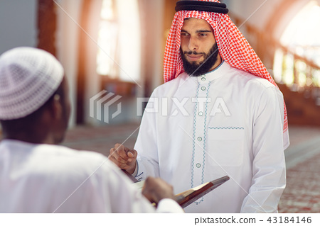 Two religious muslim man praying together inside the mosque 43184146