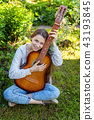 Young woman sitting in grass and playing guitar 43193845