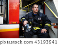 Photo of young firefighter looking to side with helmet in overalls sits in fire truck 43193941