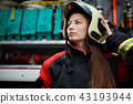 Photo of fire woman with long hair in helmet next to fire engine 43193944