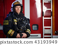 Photo of serious fireman wearing helmet with gas mask on background of fire engine with stair 43193949