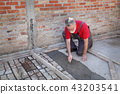 Pavement or terrace making, worker spreading mortar 43203541