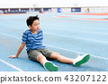 Boy rest on the blue track after sport 43207122