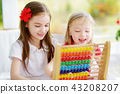 Two cute little girls playing with abacus at home 43208207