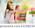 Cute little girl playing with abacus at home 43208236