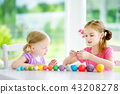 Two cute little sisters playingwith modeling clay  43208278