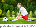 Cute little soccer player having fun playing a soccer game on summer day 43210055