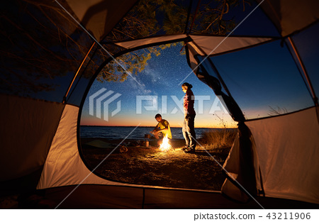 Young couple man and woman having rest at tourist tent and burning campfire on sea shore near forest 43211906