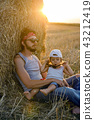 father and son in t-shirts sitting next to a haystack 43212419