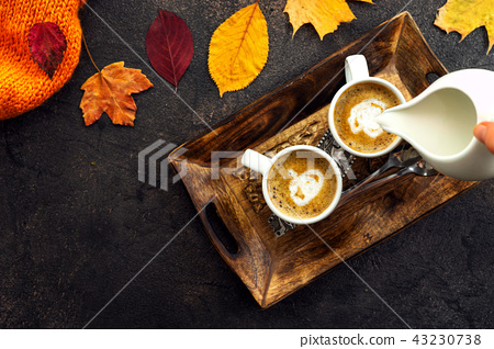 Top view of coffee cups around yellow leaves 43230738