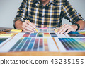 Creative graphic designer using graphics tablet to choosing colo 43235155