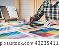 Creative graphic designer using graphics tablet to choosing colo 43235411