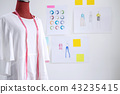 Red dummy in white clothes with measuring tape in tailors studio 43235415