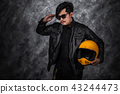 biker man in leather jacket and holding helmet 43244473