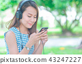 women listening to music with headphones. 43247227