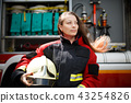 Photo of young woman with long hair looking to side next to fire engine 43254826