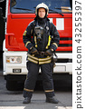 Photo in full growth of fireman on background of fire engine machine at station 43255397