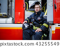 Photo of young fireman with helmet in overalls sits in fire truck 43255549