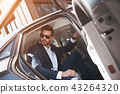Confident businessman. Fashionable man coming out of a car 43264320