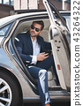 Confident businessman. Fashionable man coming out of a car 43264322