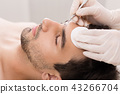 Cosmetician using blackhead remover for cleaning man face 43266704