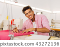 Cheerful young tailor smiling happily and enjoying his working day 43272136