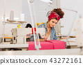 Concentrated dressmaker looking attentively at the pattern before starting sewing 43272161