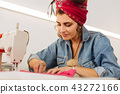 Pretty woman smiling while sitting and using her sewing machine 43272166