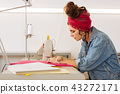Serious woman leaning to the table while sewing textile 43272171
