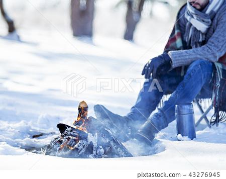 Snowy scene near bonfire. 43276945