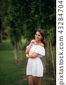 young and pretty girl in a summer city standing near the tree 43284704
