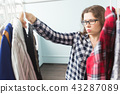 woman choosing clothes in front of full closet 43287089