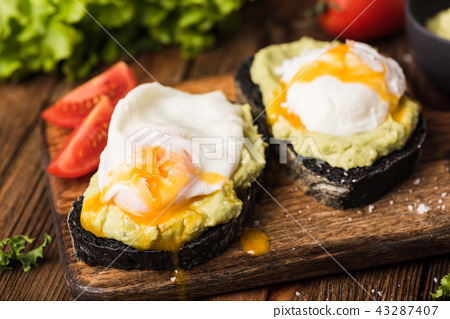 Toast with mashed avocado and poached egg, coal bread 43287407