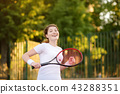 Young female tennis player with tennis ball and racket preparing to serve 43288351